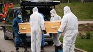 Sargträger in Schutzanzügen bringen im britischenChislehursteinen Sarg zu einem Leichenwagen