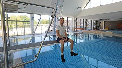 Thomas Dyck, Schwimmmeister, sitzt im leeren Zollstockbad in Köln auf einem Sprungbrett