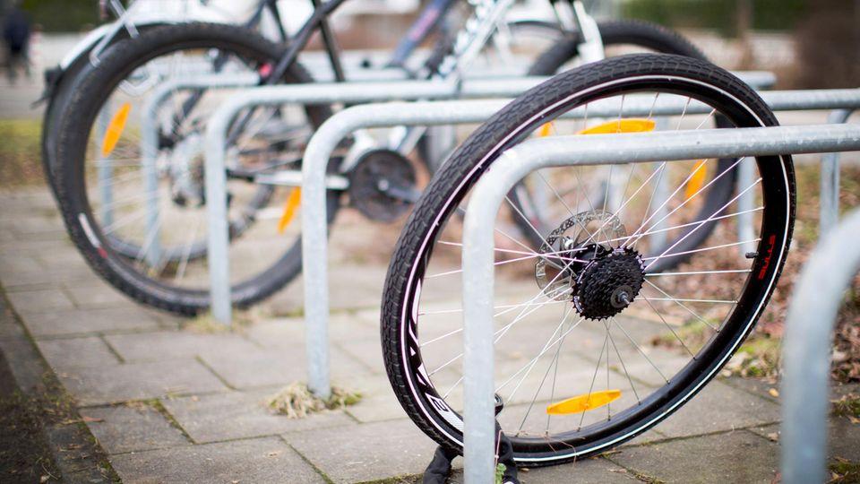 Düsseldorf: Ein zurückgelassenes Hinterrad von einem Fahrrad steht nach einem Fahrraddiebstahl an einem Fahrradständer.