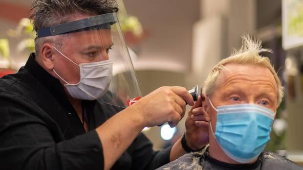 Ein Frisuer mit Atemmaske und Geischtsvisir rasiert einem Kunden mit Mundschutz die Haare am Hinterkopf