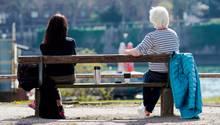 Auf einer Parkbank sitzen zwei Frauen. Rechts eine Weißhaarige, links eine Brünette. In der Lücke zwischen ihnen Kaffeebecher