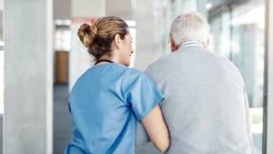 Krankenschwester stützt alten Mann