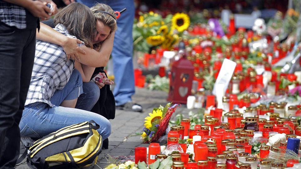 Kerzen, die die Trauer nicht mildern: Zwei Frauen am Unglücksort kurz nach der Katastrophe im Juli 2010