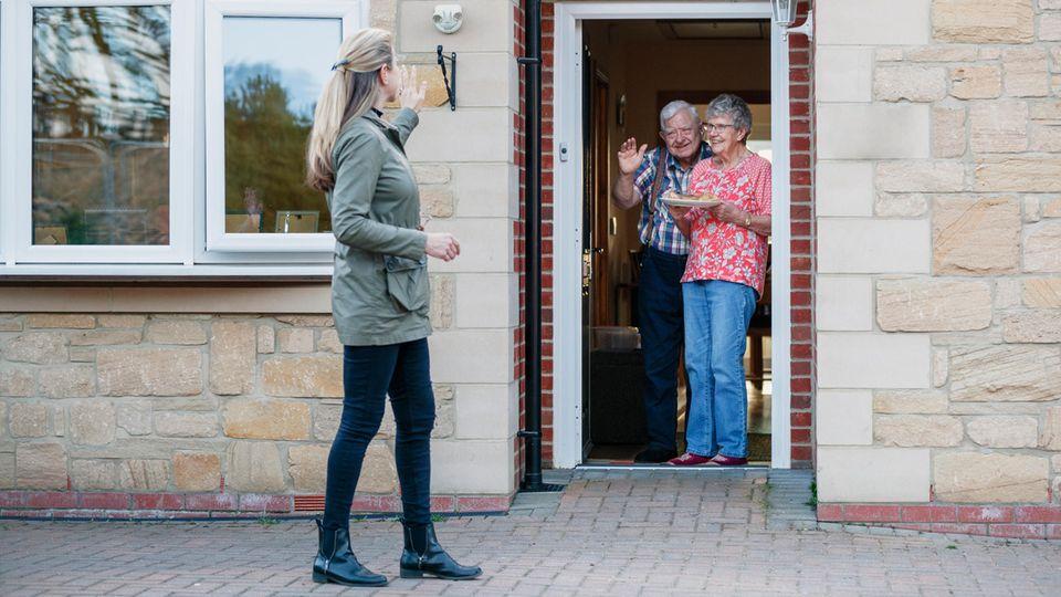 Altes Ehepaar winkt aus der Haustür einer jungen Frau