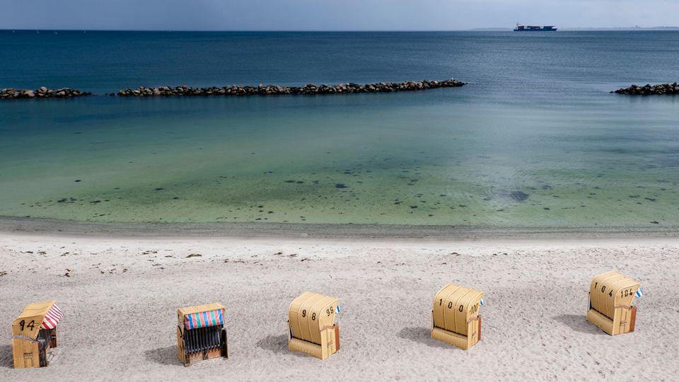 An einem Ostseestrand stehen fünf Strandkörbe in einer Reihe, während am Horizont ein Conatainerschiff vorbeifährt