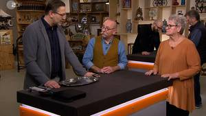 """""""Bares für Rares""""-Experte Detlev Kümmel erklärt Moderator Horst Lichter, warum in das Tablett von Ingrid Klinger eine Münze eingearbeitet ist."""