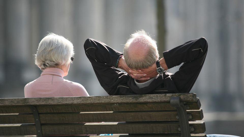 Ein älterer Mann und eine ältere Frau sitzen auf einer Bank, von hinten fotografiert