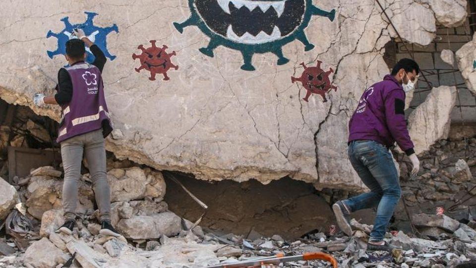 Mit Graffiti warnen Helfer in Idlib vor Corona
