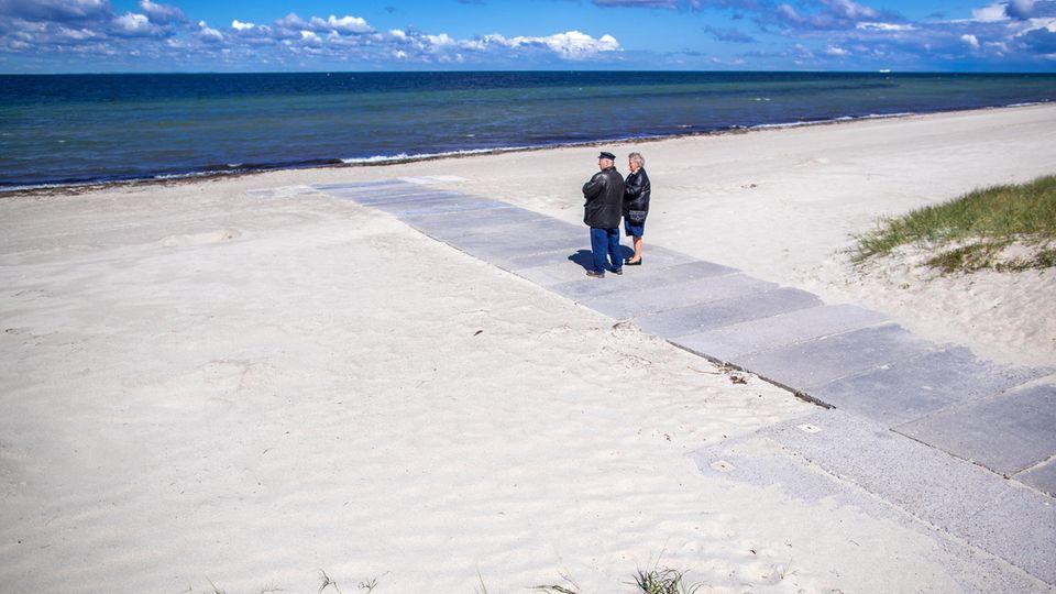 Rentnerpaar am ansonsten menschenleeren Strand in Timmendorf