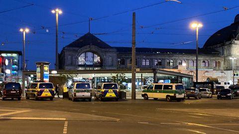 Im Dunklen stehen vor dem Hauptbahnhof in Nürnberg eine Reihe Polizeiwagen unter Laternen