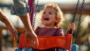 Ein kleines Mädchen sitzt strahlend auf einer Schaukel