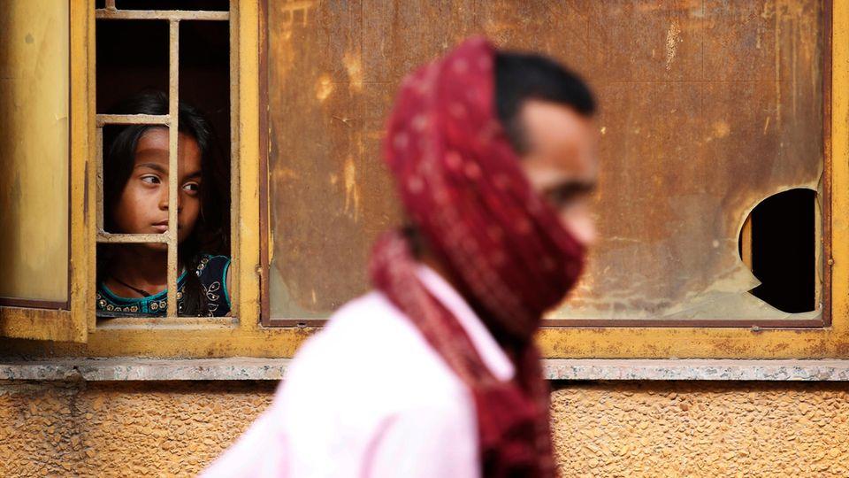 Ein Mädchen schaut aus einem Fenster einer staatlichen Schule in der indischen Hauptstadt Neu Delhi.