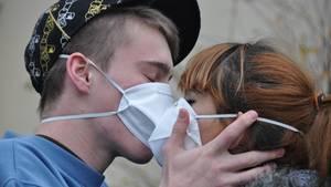 Junges Paar küsst sich mit Masken