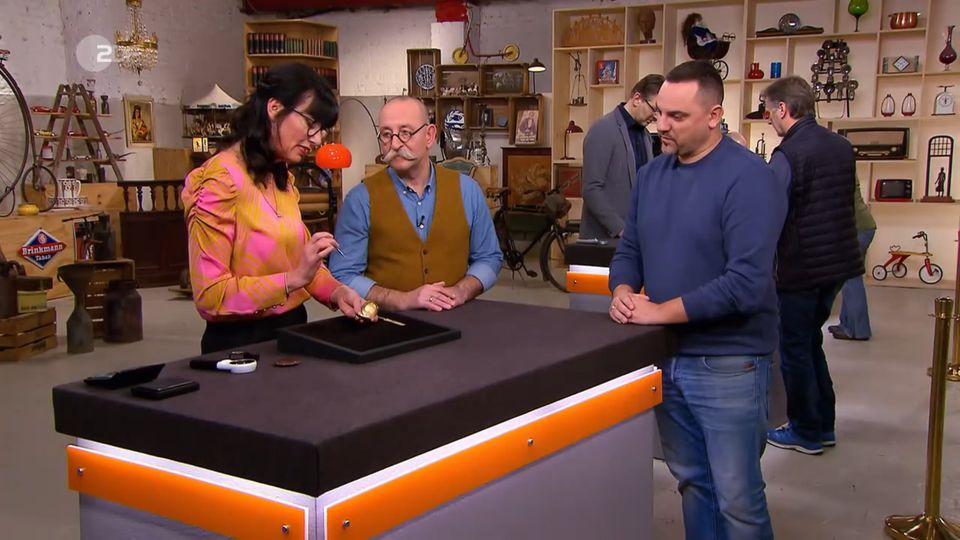 """""""Bares für Rares""""-Expertin Heide Rezepa-Zabel zeigt Moderator Horst Lichter das Uhrwerk der Taschenuhr vonMarkus Krutzke."""