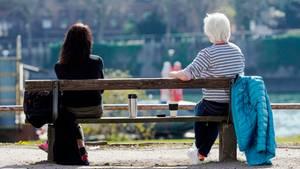 Zwei Frauen sitzen mit Abstand zueinander auf einer Parkbank