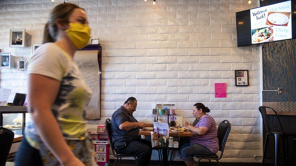 Servicekraft mit Maske und Gäste im Restaurant
