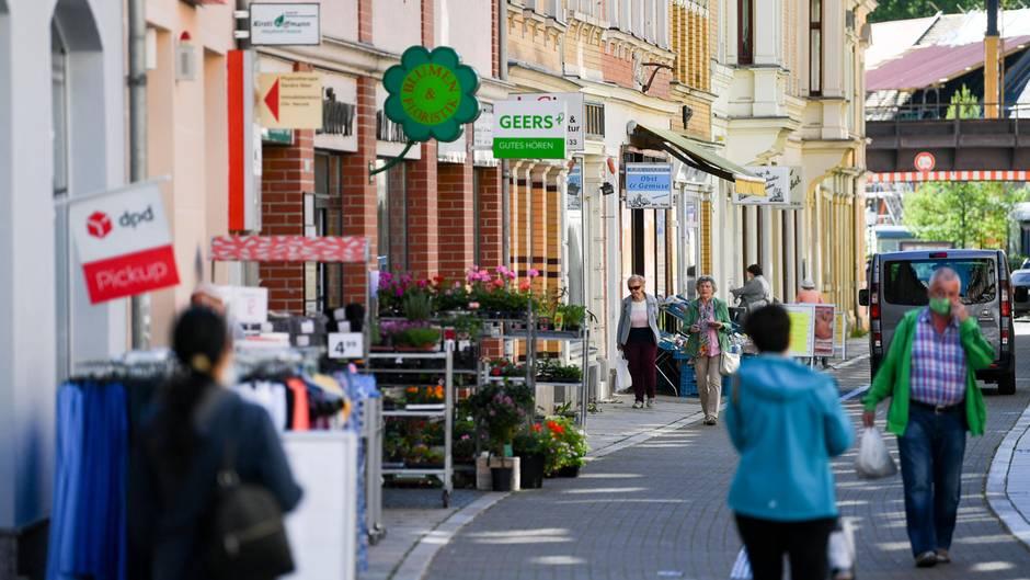 Thüringen, Greiz: Besucher der Innenstadt von Greiz gehen durch eine Einkaufsstraße im Zentrum der Altstadt