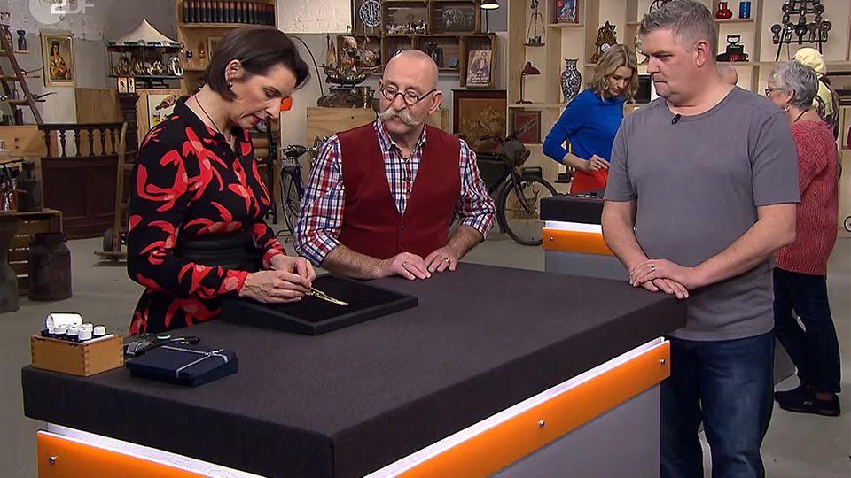 """""""Bares für Rares""""-Expertin zeigt Moderator Horst Lichter die gute Verarbeitung des Goldarmbands von Frank Wolf."""