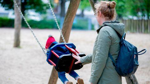 Eine Mutter in graugrünem Parka schubst auf einem Spielplatz ein Kind mit roter Mütze auf der Schaukel an