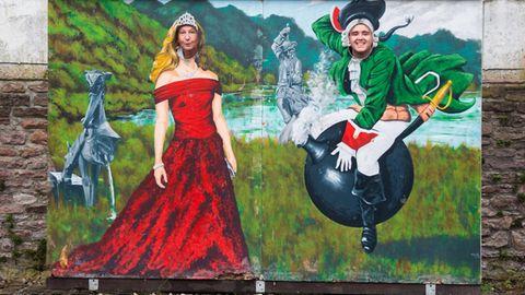 Museumsdirektorin Claudia Erler und Mitarbeiter Kevin Otte schauen durch eine Wand mit einem Bild des Barons von Münchhausen auf der Kanonenkugel am Münchausen-Museum Bodenwerder