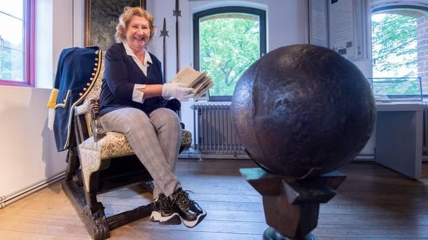 Museumsdirektorin Claudia Erler sitzt mit einem historischen Buch im Münchausen-Museum Bodenwerder