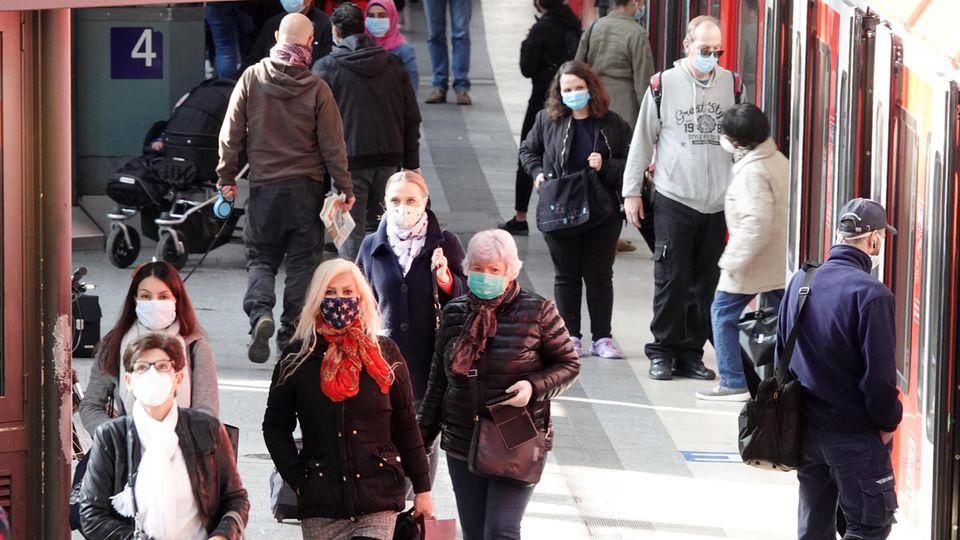Mit Mundschutz sind Fahrgäste am Hamburger Hauptbahnhof auf einem Bahnsteig unterwegs