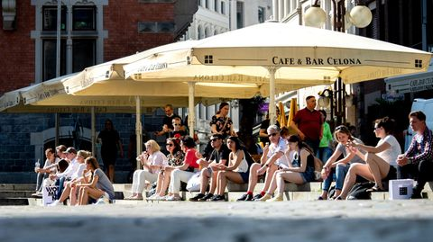 Zahlreiche Menschen sitzen in der Innenstadt von Oldenburg auf den Treppen am Rathausmarkt, wo sonst die Tische und Stühle der Gastronomie unter Schirmen stehen