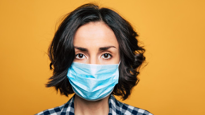 Corona Selbsttest: Eine Frau mit Mundschutz blickt in die Kamera