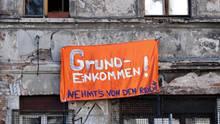 """Ein Banner mit der Aufschrift """"Grundeinkommen! Nehmt's von den Reichen"""""""