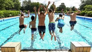 Kinder springen ins Freibad