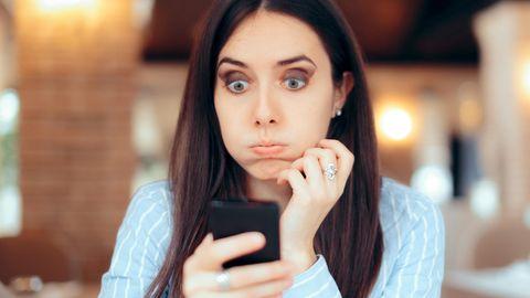 Frau schaut genervt auf ihr Smartphone
