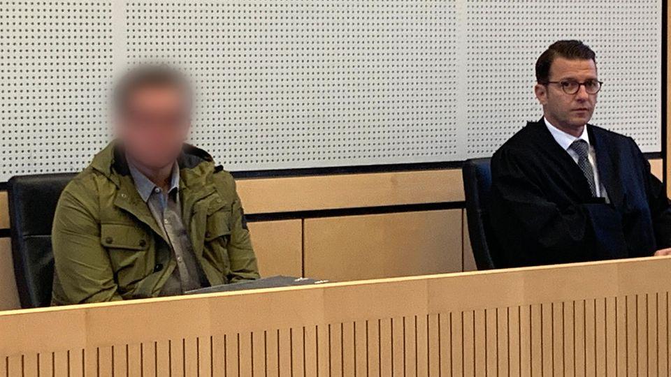 Der Angeklagte sitzt im Gerichtssaal neben seinem Verteidiger