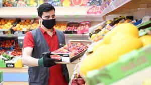 Mitarbeiter eines Lebensmittelgeschäfts füllt in der Gemüseabteilung ein Regal auf