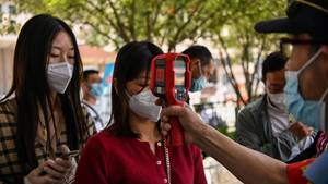 Bei einer Frau in Wuhan wird die Temperatur gemessen