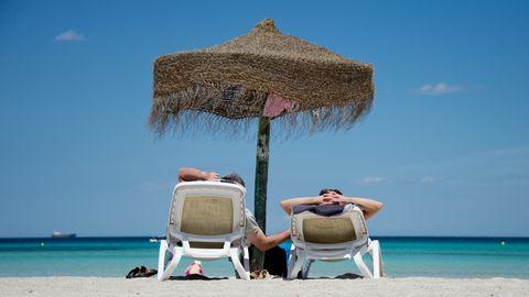Deutsche Urlauber liegen an einem Strand im Norden der Mittelmeerinsel Mallorca