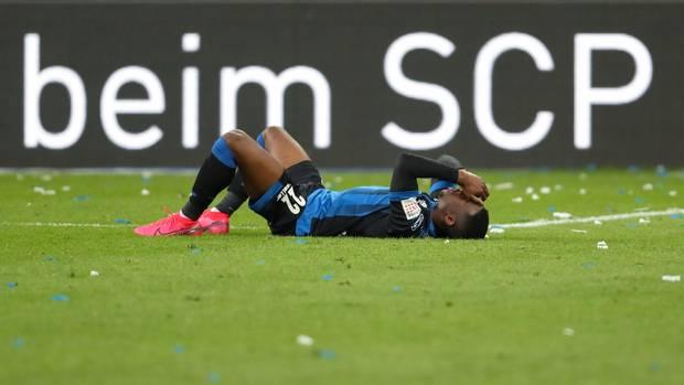 """Paderborn-Spieler Christopher Antwi-Adjej liegt auf dem Rasen vor einer Bande mit der Aufschrift """"beim SCP"""""""