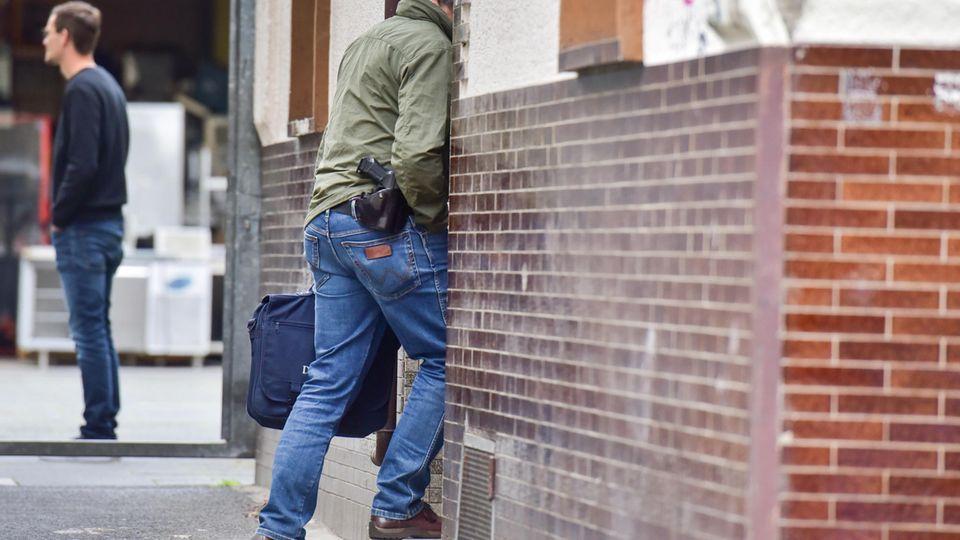 Ein Polizeibeamter betritt ein Haus in Bonn.