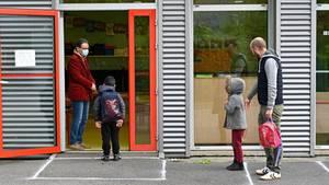 Schüler in Frankreich warten mit Abstand voneinander vor der Tür