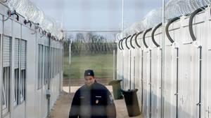 Ein Wachmann geht durch eine leere Containerstraße mit Stacheldraht im Asylbewerberheim Röszke in Ungarn