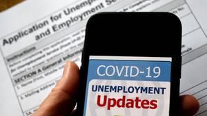 Ein Handy vor einem Arbeitslosenhilfe-Antrag