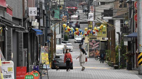 Passanten laufen durch den StadtteilItaewon in Seoul. Nachdem dort die Nachtclubs und Bars wieder geöffnet hatten, ist ein neuer Corona-Hotspot entstanden.