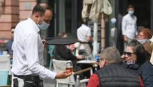 Ein Kellner mit Mundschutz bedient Gäste im Außenbereich eines Lokals
