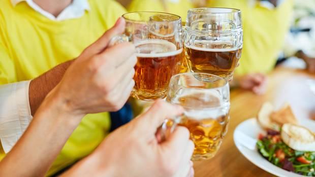 Gäste im Restaurant stoßen mit Bier an