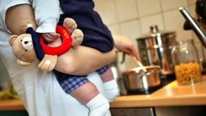 Eine Mutter hält beim Kochen ihr Kleinkind auf dem Arm