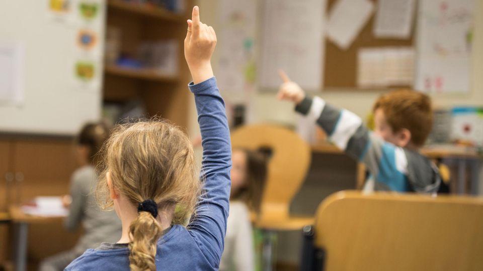Eine Grundschülerin meldet sich im Unterricht