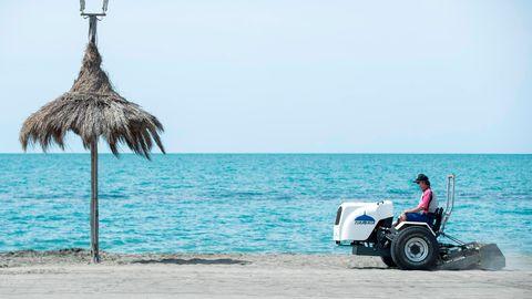 Ein Mann auf einem Fahrzeug bereitet einen Strand auf die Wiederöffnung im Sommer vor