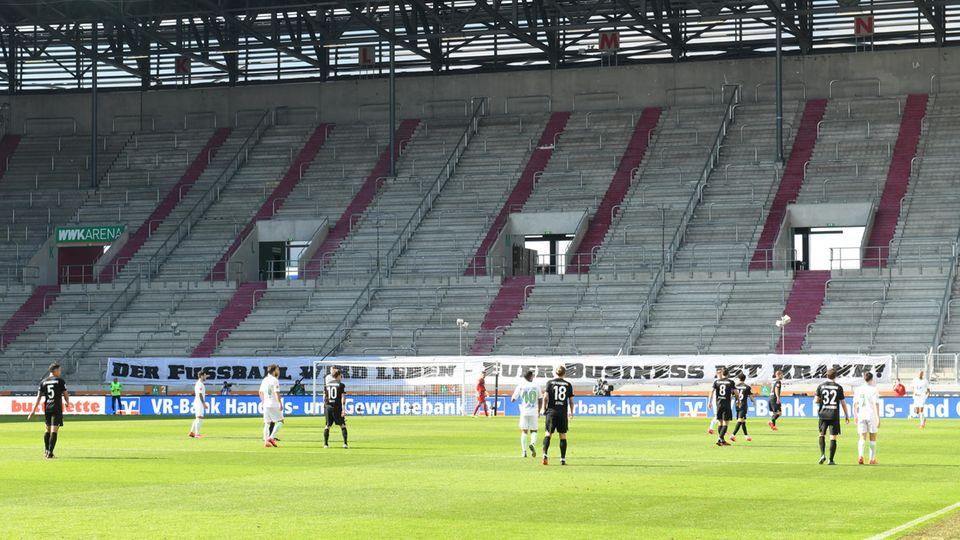 """""""Der Fußball wird leben - Euer Business ist krank"""", steht auf einem Banner im Stadion des FC Augsburg"""