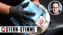 Ein Balljunge desinfiziert während der Partie Karlsruher SCgegen denSV Darmstadt 98 den Ball. Am Samstag startete die Bundesliga unter Hygiene-Auflagen.