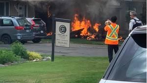 Flammen schlagen aus einem Flugzeugwrack, das hinter einem Parkplatz auf den Boden geprallt ist. Ein Mann filmt den Brand