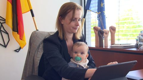 FDP-Abgeordnete Gyde Jensen sitzt mit ihrer Tochter vor dem Schreibtisch im Bundestag.